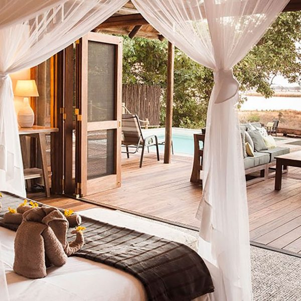 The bed and outdoor seating area of the Safari Suite