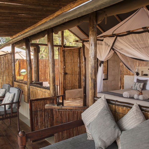A 4-poster bed is located in the centre of the chalet, looking out over the verandah and river in front of the room