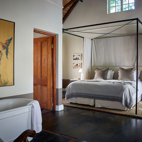 An open area bedroom with prominent four-poster bed with natural linen and modern styling. The bath is in the same bedroom, with a door leading off to a separate bathroom