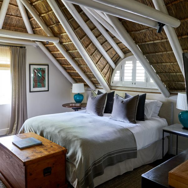 Image of a bed with linen in natural colours and a thatch roof with white beams. Sun streams in from the window next to the bed