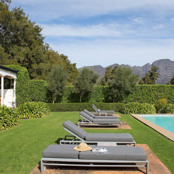 View of a generously sized lap pool stretching into the distance, with three sets of double sun loungers positioned to the left and mountain views to the right