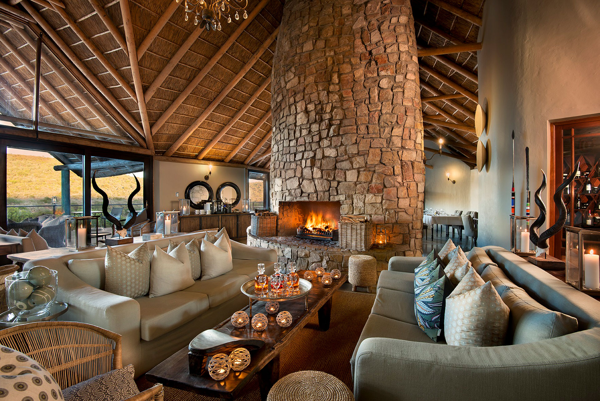 The lounge at Great Fish River Lodge with couches, tables and a fireplace