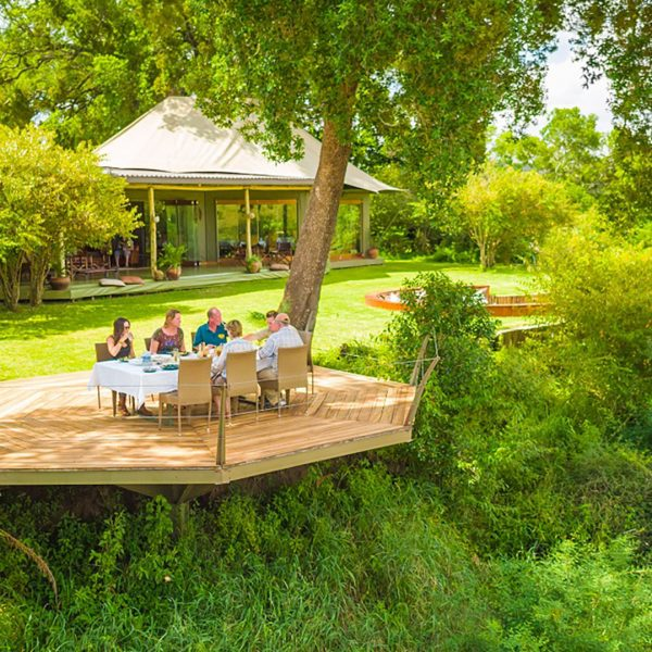 Guests enjoy lunch on the outside deck, under the trees