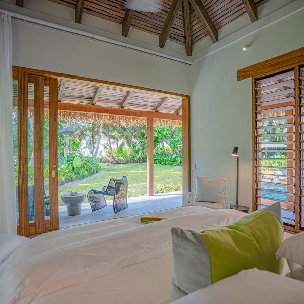 One of the master bedrooms in the Beach Villa, with stacking doors opening onto a small deck and towards the private entrance to the beach - Blue Safari Seychelles