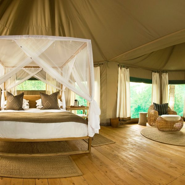 The interior of the Chindeni tented rooms with a 4 poster bed and seting area