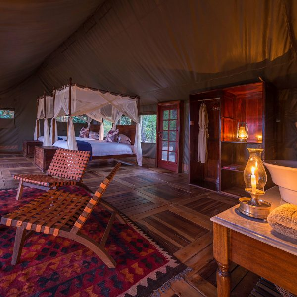 The interior of the room at Zungulila with a desk, lounge area, beds with mosquito nets, and an en-suite bathroom