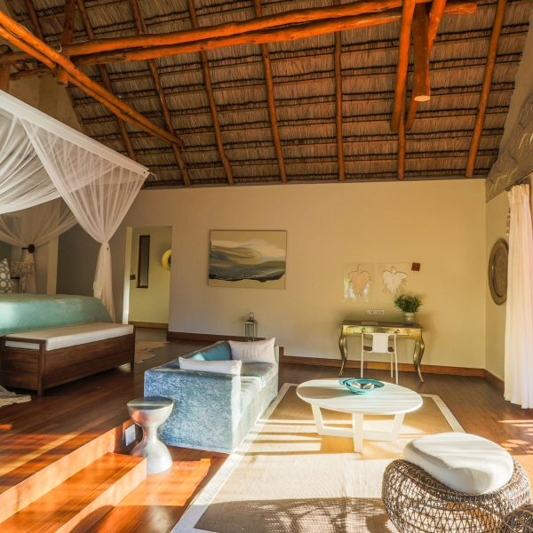 4 poster bed, seating area, and stacking doors leading onto the patio in the Presidential Villa