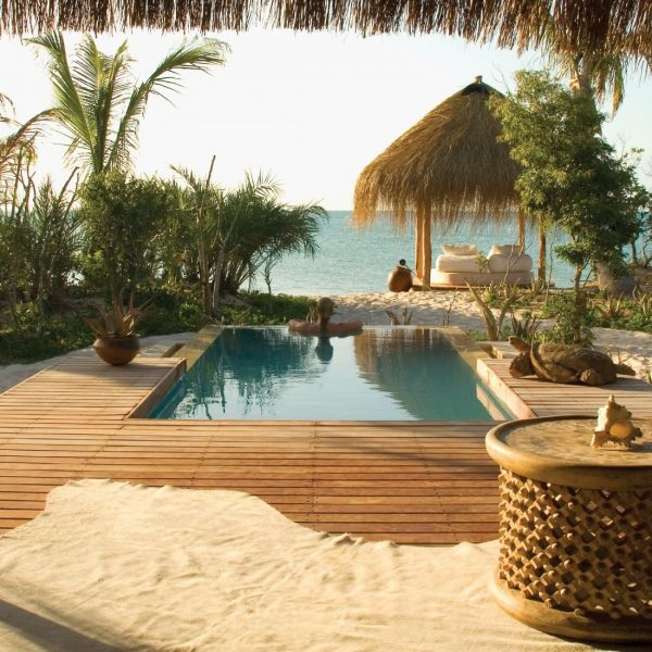 view looking out over the pool, beach and outdoor sala