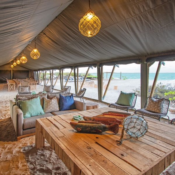 Inside the main tent area of Cosmoledo Eco Camp, with tables, couches, and chairs on the sand - Blue Safari Seychelles