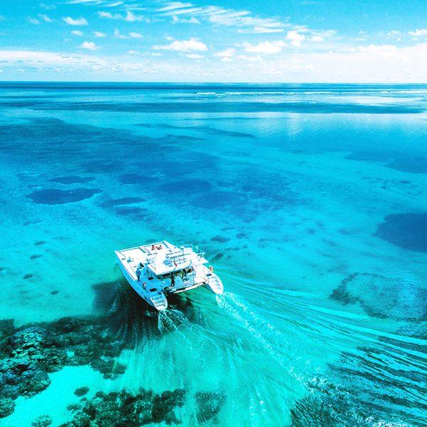 The ocean cruiser boat moving across the flat, clear blue water - Blue Safari Seychelles