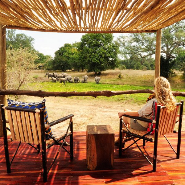 A guests enjoying a sit on the private deck of her room while watching elephants drink along the side of the river