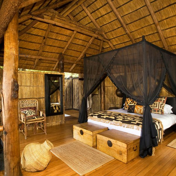 The interior of Chamilandu with a king bed and mosquito net, and en-suite bathroom
