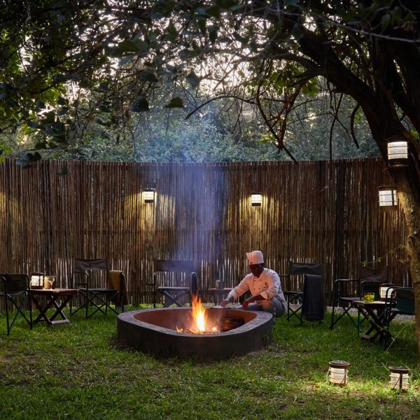 A chef prepares a fire pit in the backyard of the Director's House