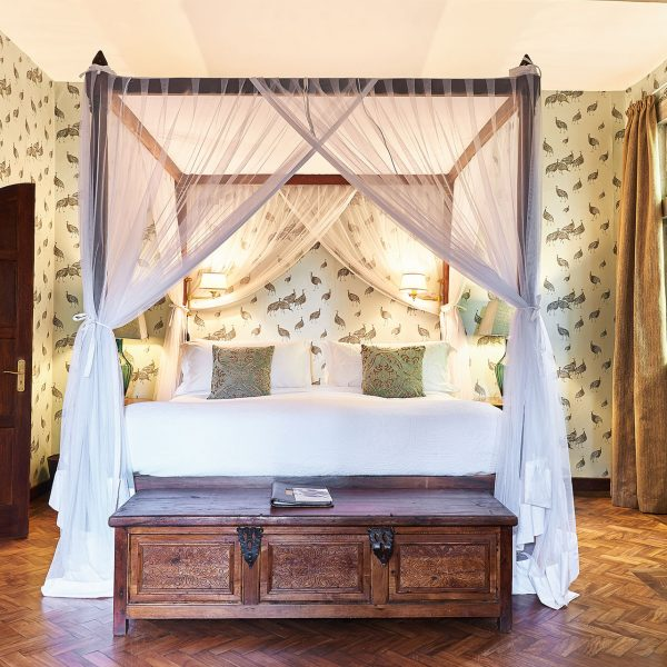 Edd's Room at Giraffe Manor with a 4-poster bed and mosquito net, and en-suite bathroom
