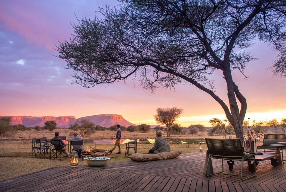 the outside deck and fire pit area looking out over a waterhole and the Waterberg Mountains