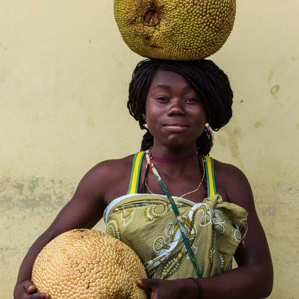 A local woman carries two Jaca fruits