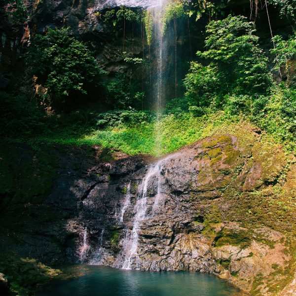 A guests swimming in a natural pool at the bottom of a waterfall