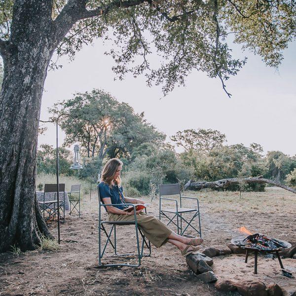 Lady reading a book under the shade of a tree at Tanda Tula Field Camp