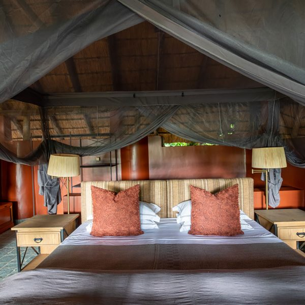The interior of the room at Kapamba with the king bed inside a mosquito net