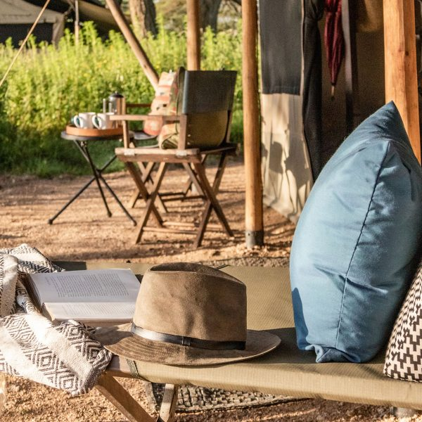 An outdoor table and chairs, and lounger outside of your tent