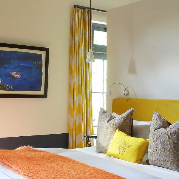 A bedroom at the Galerie with a large bed and open plan, en-suite bathroom behind the bed