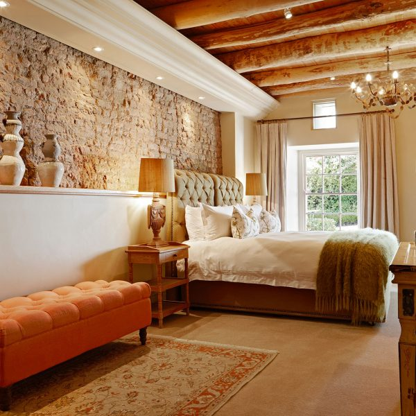 A guest room at the Grange with a large bed and original brick wall