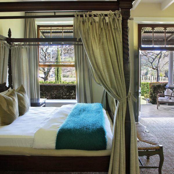 A guest room with a 4-poster bed, tea/coffee station, and doors leading out to the terrace outside