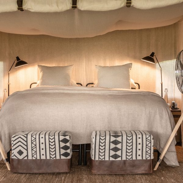 A king bed with bedside tables and lamps as well as fans, underneath mosquito netting