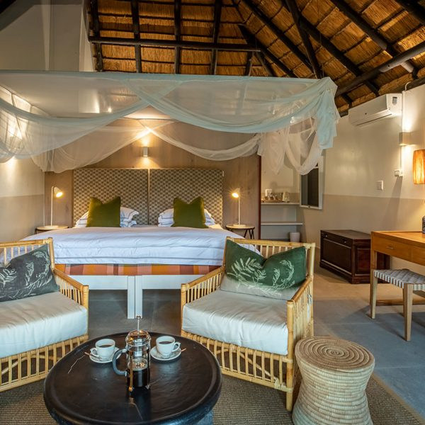 The interior of a new room at Mfuwe Lodge with a king bed and mosquito net plus desk and lounge area
