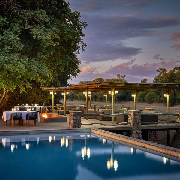 The pool and outdoor area is transformed to a stunning dinner location at night, with hanging lights and private settings