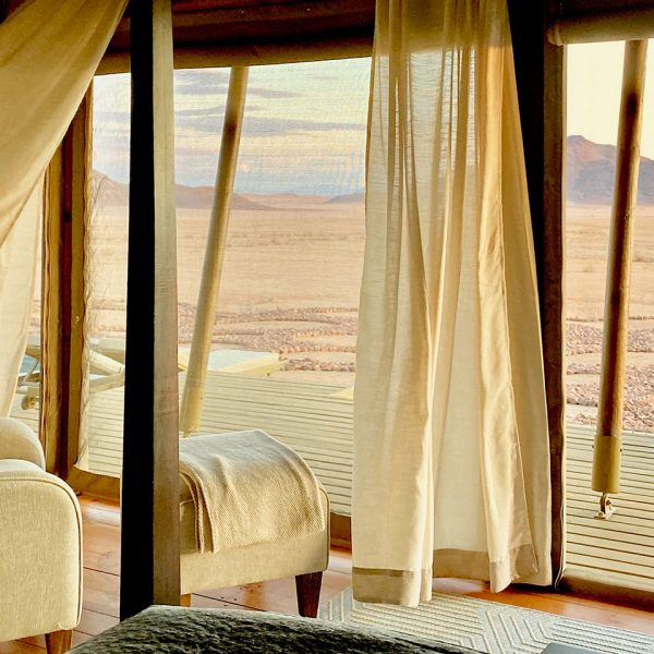 A guest sits on her outside deck of her room looking out over the plains