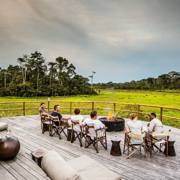 Guests sitting on the front deck of Lango Camp watching the wildlife below them