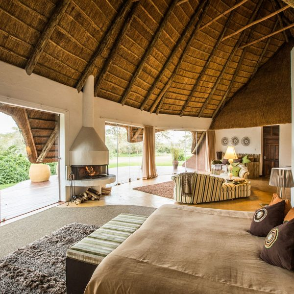The interior of the rooms at Solio Lodge with a large bed, fireplace, lounge, and en-suite bathroom