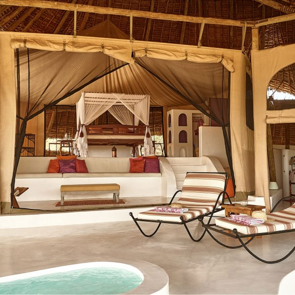 The interior and exterior of the Sasaab room, with a large bed and mosquito net, outside loungers, lounge area, and private pool