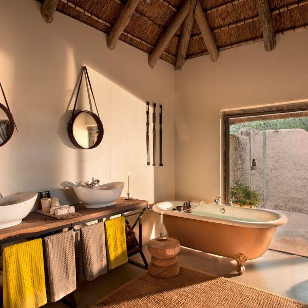 Double vanity, indoor bathtub and outdoor shower at Safari Camp