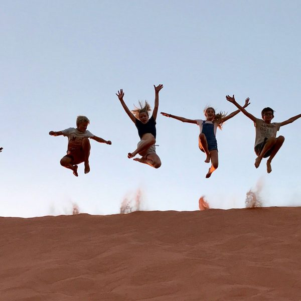 Kids jump for joy from the top of a sand dune